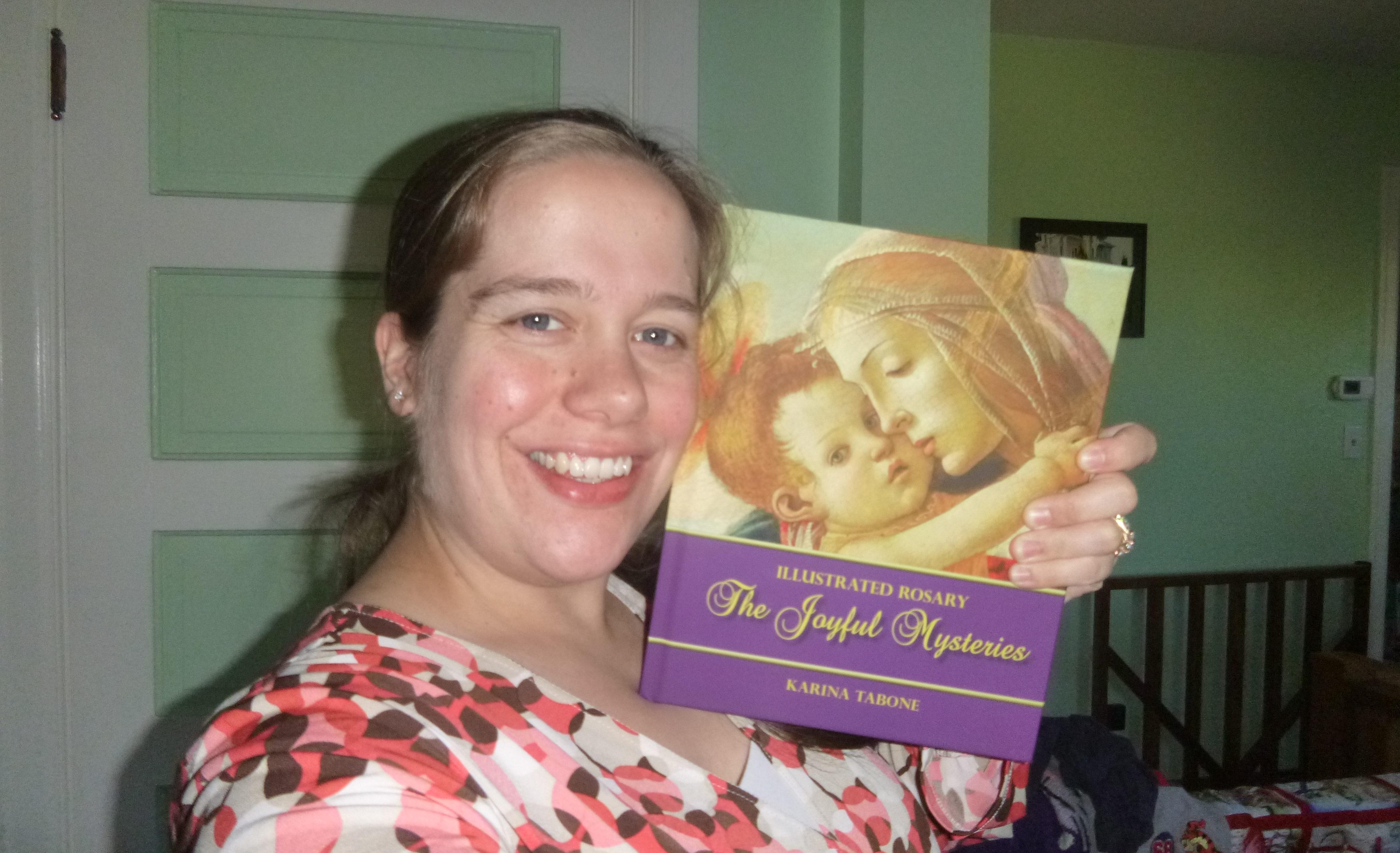Karina Tabone holding up her first book, The Joyful Mysteries. Via IllustratedPrayer.com